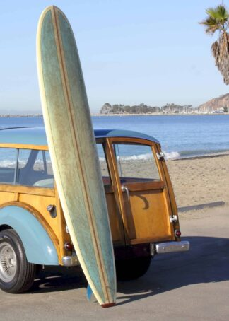 Surfboard beside the yellow car at the beach poster
