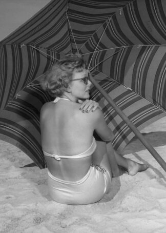 Woman sitting on the beach under umbrella poster