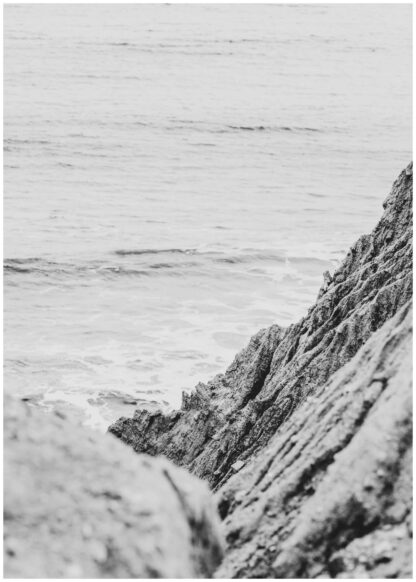 Rock formation beside body of water poster
