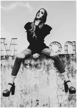 Girl sitting on concrete wall poster